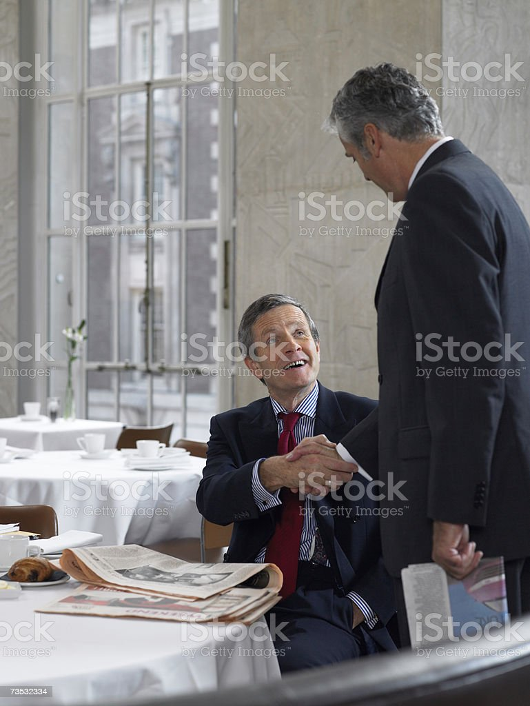 Colleagues exchanging greetings in restaurant royalty-free stock photo