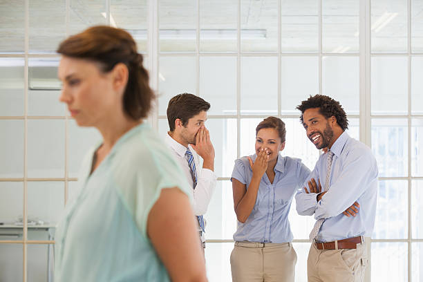 Colleagues gossiping with sad businesswoman in foreground Colleagues gossiping with sad young businesswoman in foreground at a bright office harassment stock pictures, royalty-free photos & images