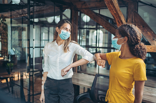Businesswomen with protective masks meeting in the office
