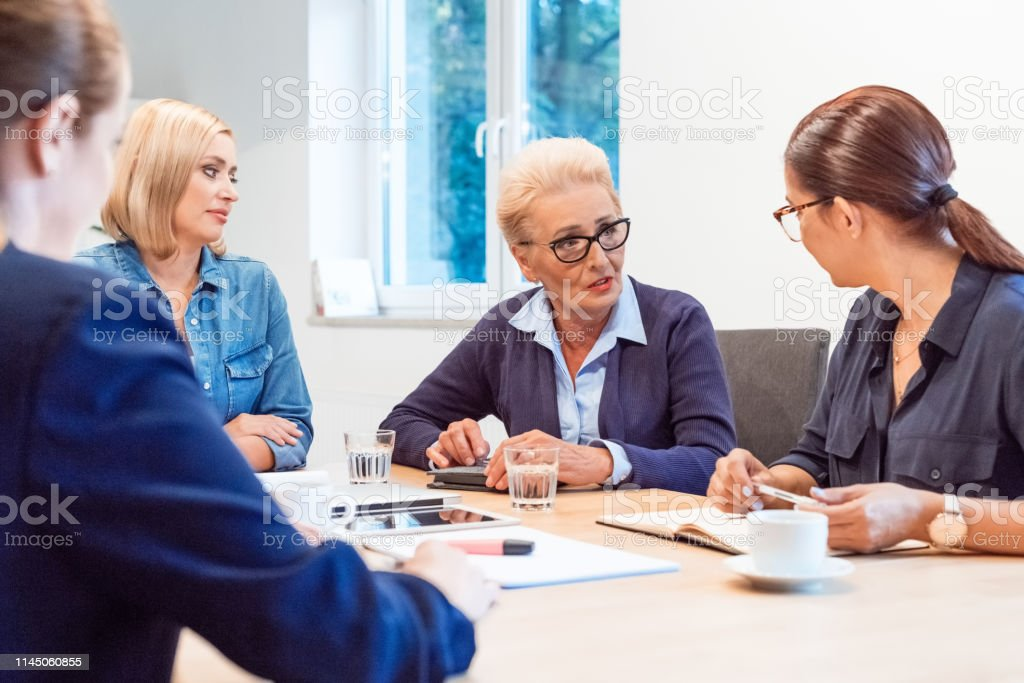 Colleagues having business discussion in meeting Female colleagues having business discussion at meeting. Confident entrepreneurs are planning strategy in office. They are sitting in board room. 35-39 Years Stock Photo