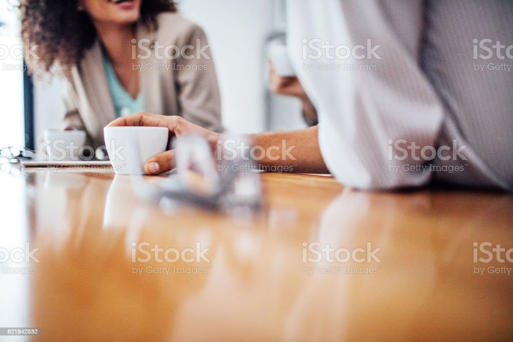 Colleagues having discussing during coffee break stock photo