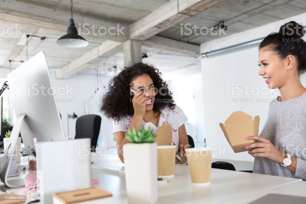 Colleagues having lunch break at office Two happy young woman sitting at the desk chatting while having lunch. Cheerful young female coworkers taking lunch together at their desk. 20-24 Years Stock Photo