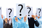 istock Colleagues holding question mark signs in front of their faces 121197933