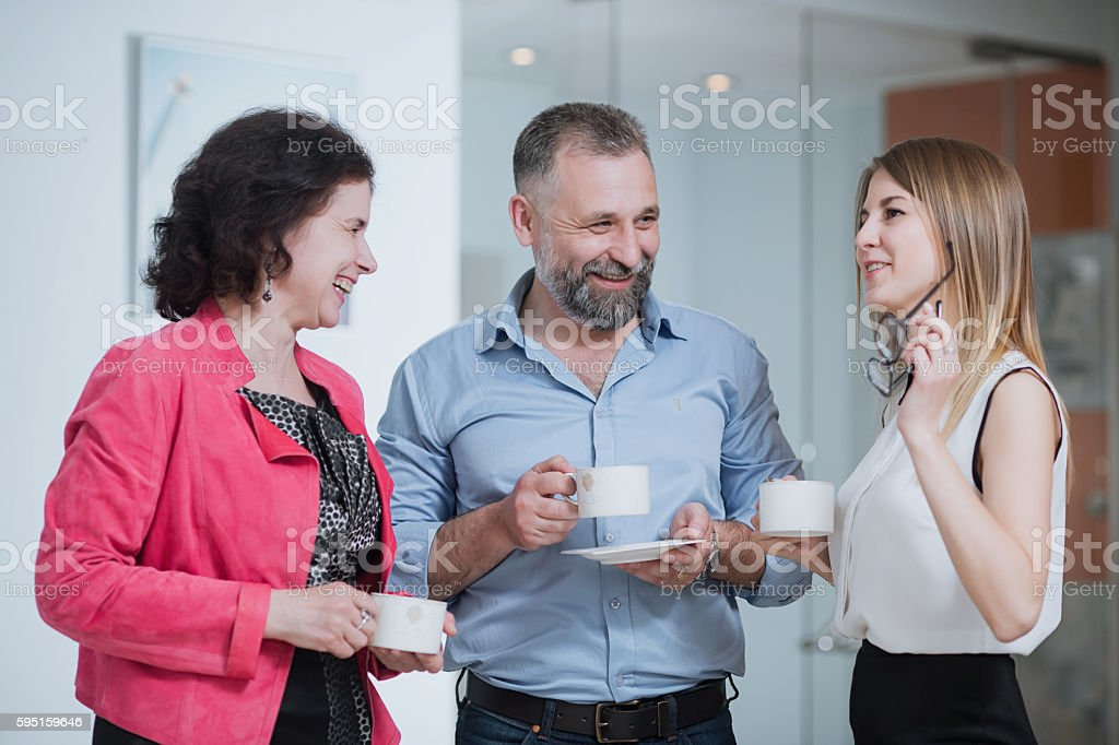 colleagues in the office talking during the coffee break stock photo