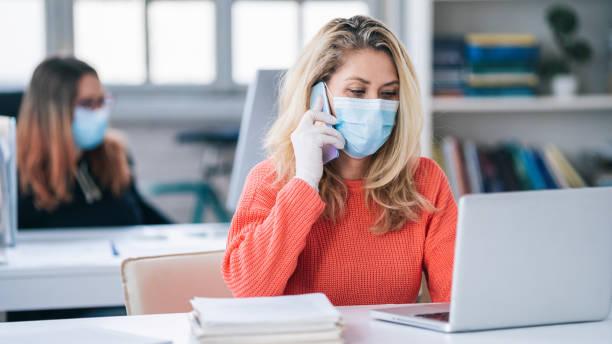 Kollegen im Büro arbeiten während des Tragens medizinischer Gesichtsmaske während COVID-19 – Foto