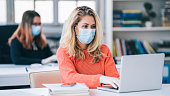 Colleagues in the office working while wearing medical face mask during COVID-19