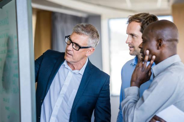 colleagues listening to businessman in meeting - business meeting imagens e fotografias de stock