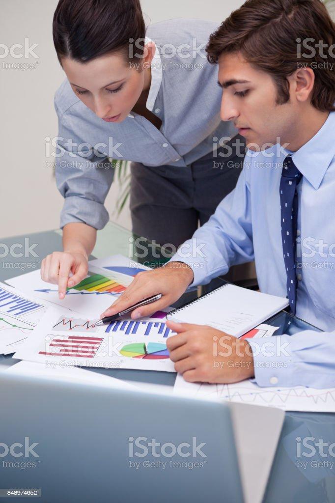 Colegas a olhar para gráficos de negócios no escritório - foto de acervo