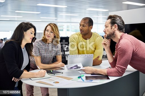 1150572092istockphoto Colleagues looking at businesswoman in meeting 1072465584