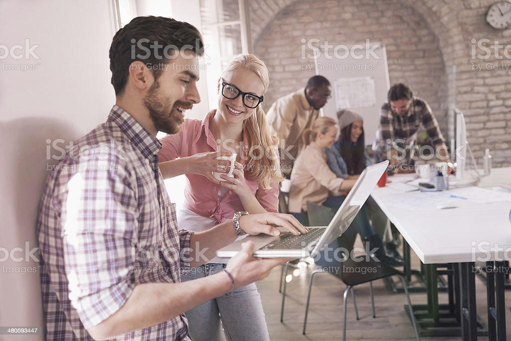 Colleagues looking at laptop royalty-free stock photo