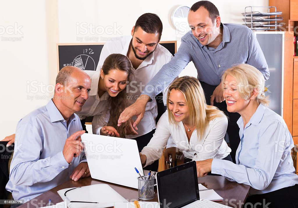 Colleagues looking at laptop stock photo