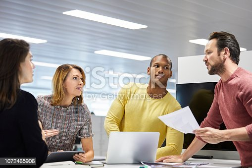 1150572092istockphoto Colleagues looking at mature businessman at table 1072465906