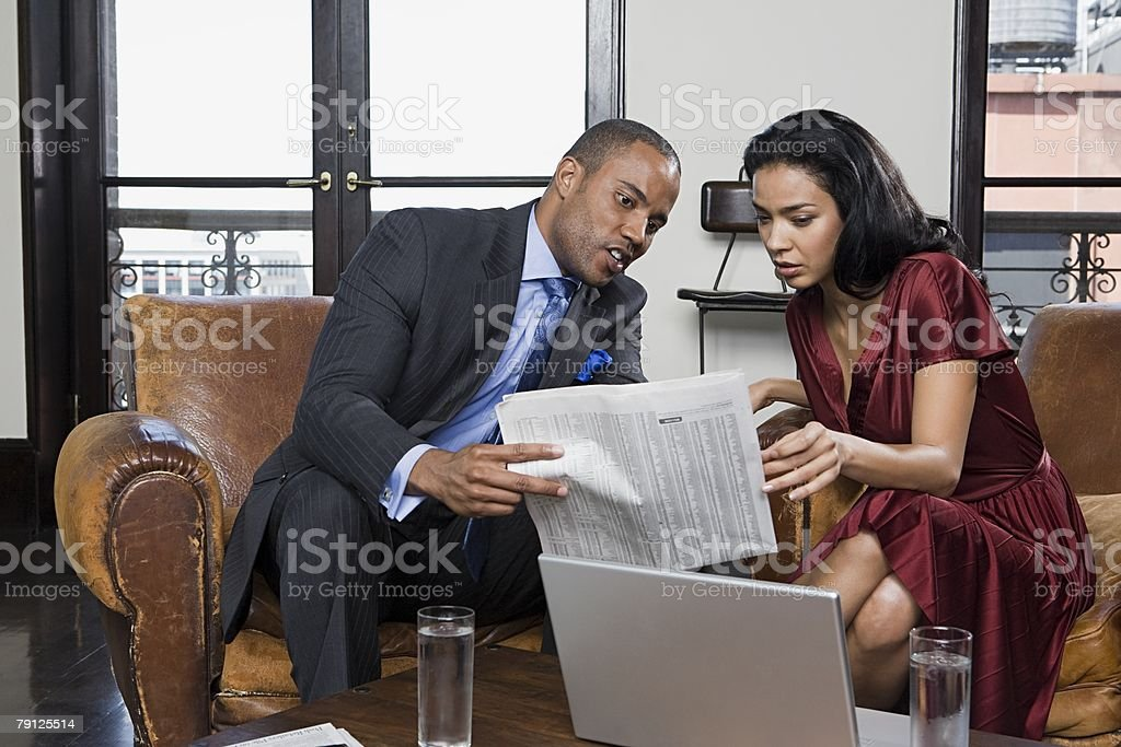 Colleagues looking at newspaper 免版稅 stock photo