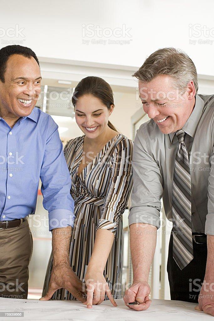 Colegas olhando para planos e sorrir foto de stock royalty-free