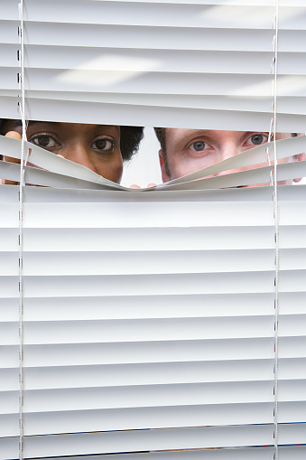 istock Colleagues looking through blinds 535024705
