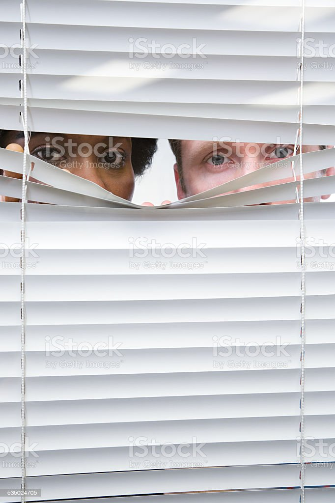 Colleagues looking through blinds stock photo