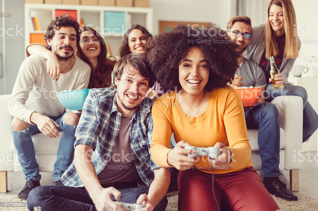 Colleagues playing video games in the office relax room stock photo