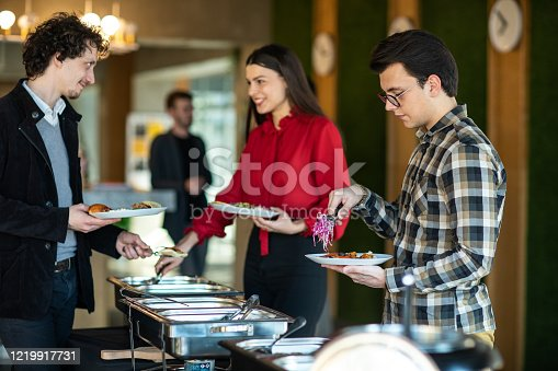 Happy colleagues serving themselves at buffet after work at self service restaurant