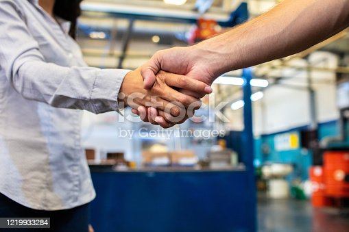 Close-up shot of businesswoman shaking hands with factory worker.  Colleagues shaking hands in factory shop floor.
