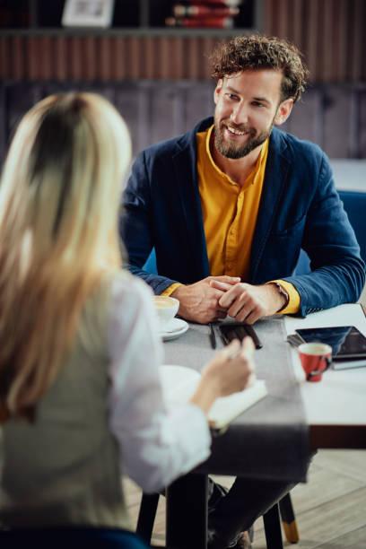 Kollegen sitzen im Café und reden über Geschäfte. – Foto