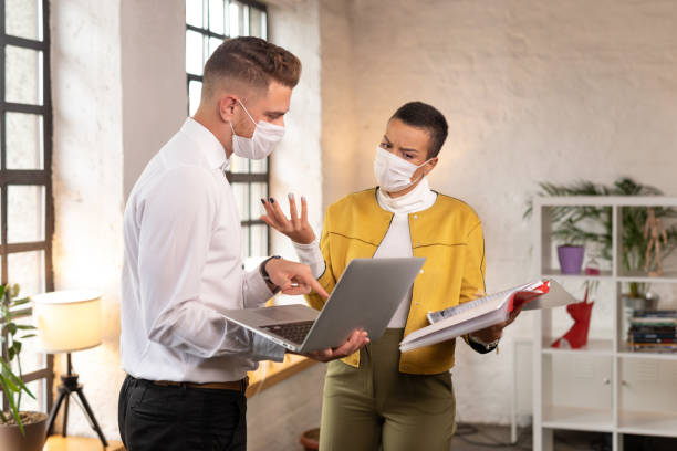 Colleagues standing at distance wearing protective face masks and arguing at office during COVID-19 pandemic stock photo