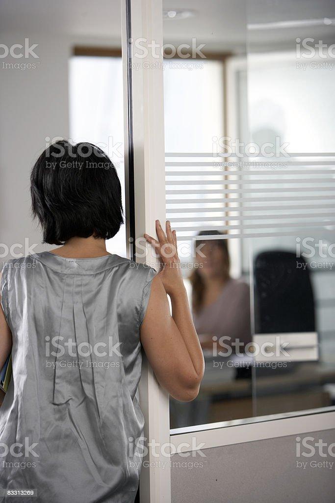 Współpracownikami rozmawiać w biurze przez drzwi zbiór zdjęć royalty-free