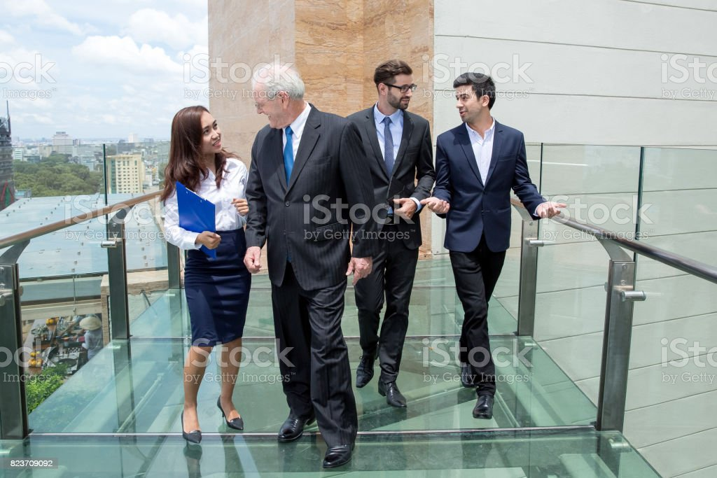 Colleagues Talking and Walking on Glass Bridge stock photo