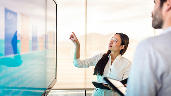 Businessman and businesswoman discussing finance in front of a screen with a graph.
