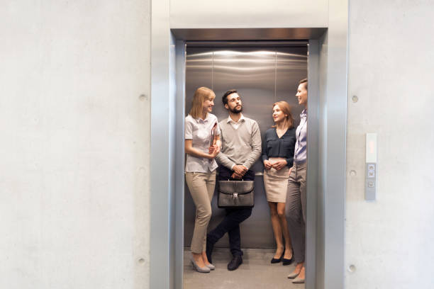 colleagues talking while standing in elevator at office - ascensore foto e immagini stock