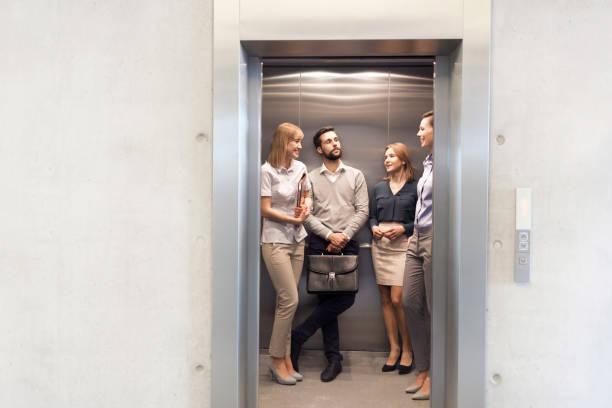 Kollegen reden, während sie im Aufzug im Büro stehen – Foto