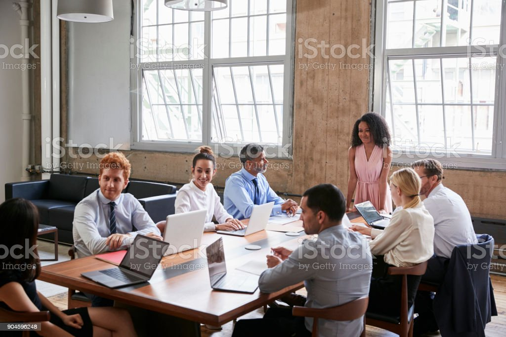 Colleagues turning to a woman at a boardroom meeting stock photo