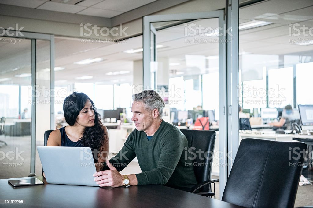 Colleagues using laptop in modern office stock photo