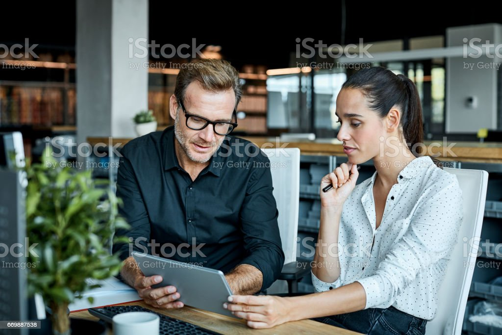 Colleagues using tablet PC in textile factory stock photo