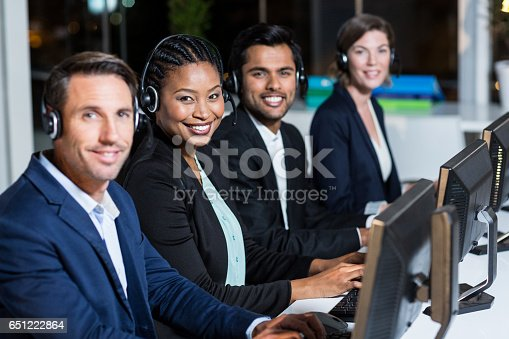istock Colleagues with headsets using computer at office 651222864