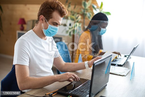 1124783373 istock photo Colleagues with protective face masks using laptops at modern office 1250025592