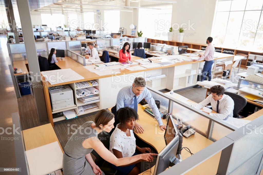 Colleagues working at a womanâ'u20acs workstation in a busy office stock photo