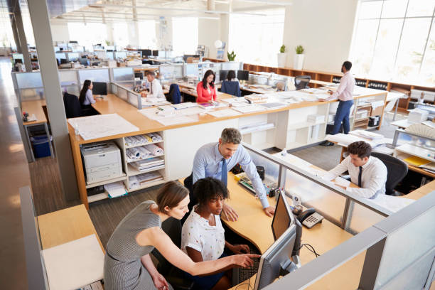 """Colleagues working at a womanâ""""u20acs workstation in a busy office Colleagues working at a womanâ""""u20acs workstation in a busy office busy stock pictures, royalty-free photos & images"""
