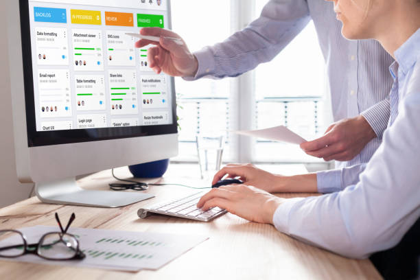Colleagues working on agile product development board with scrum or kanban framework, lean methodology, iterative or incremental organization project management strategy for startup or software design stock photo