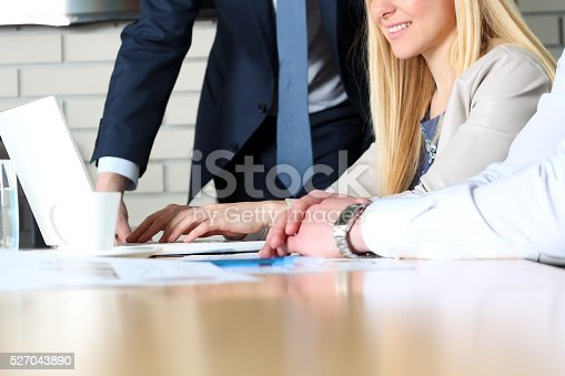 672116416istockphoto Colleagues working together and analyzing financial figures on a laptop 527043890