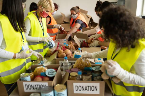 recolectar alimentos para su donación en un refugio para personas sin hogar - giving tuesday fotografías e imágenes de stock