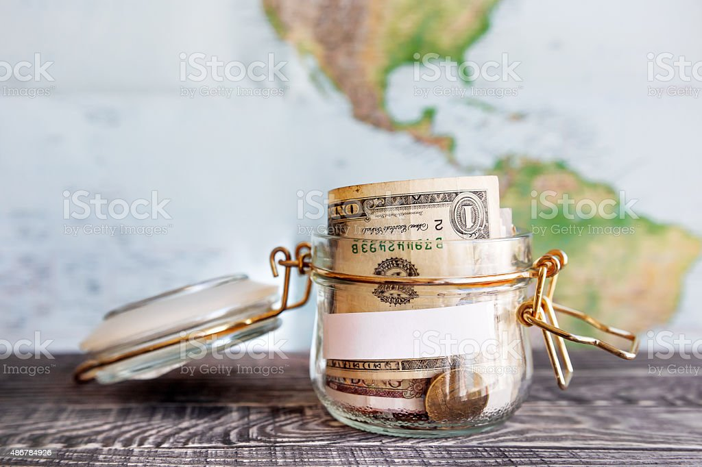 Collecting money for travel. Glass tin as moneybox with cash Collecting money for travel. Glass tin as moneybox with cash savings (banknotes and coins) on wooden table and map as background. White empty paper for text. 2015 Stock Photo