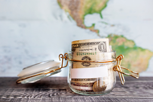 Collecting Money For Travel Glass Tin As Moneybox With Cash Stock Photo - Download Image Now