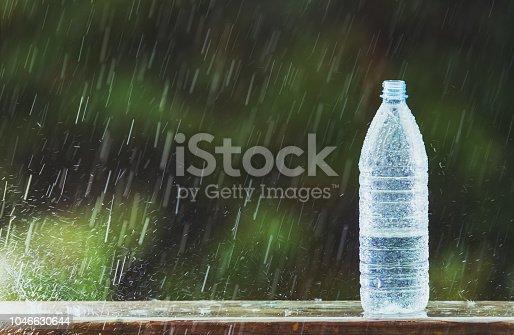 Heavy rain fills a water bottle.