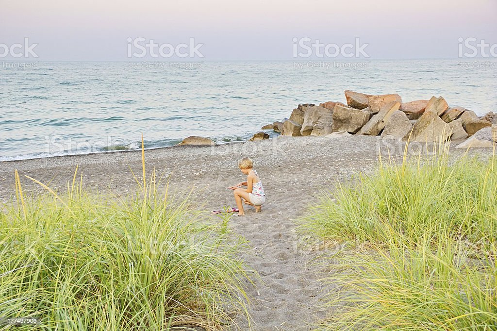 Collecting Rocks and Shells Lakeside at Dusk royalty-free stock photo