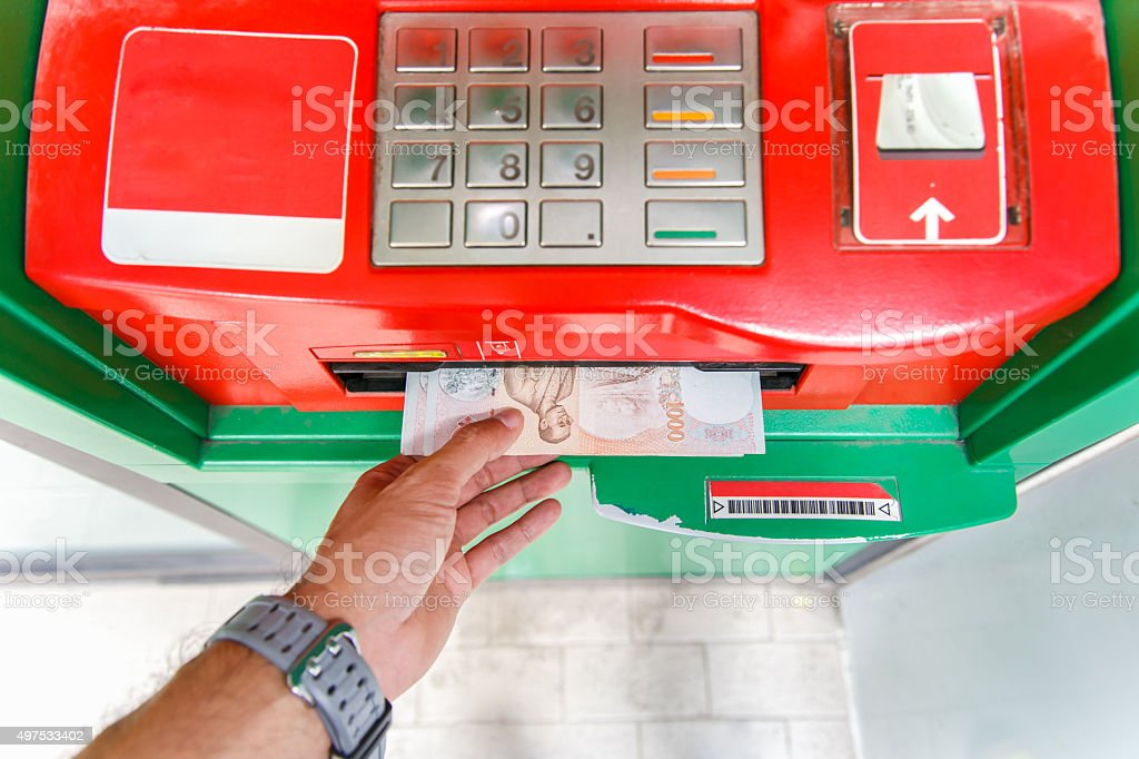 Collecting thai 1000 baht notes at ATM machine. stock photo