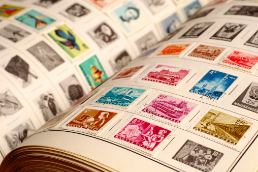 Closeup color photo of a vintage stamp album with colorful old stamps.  Selective focus on front stamps.