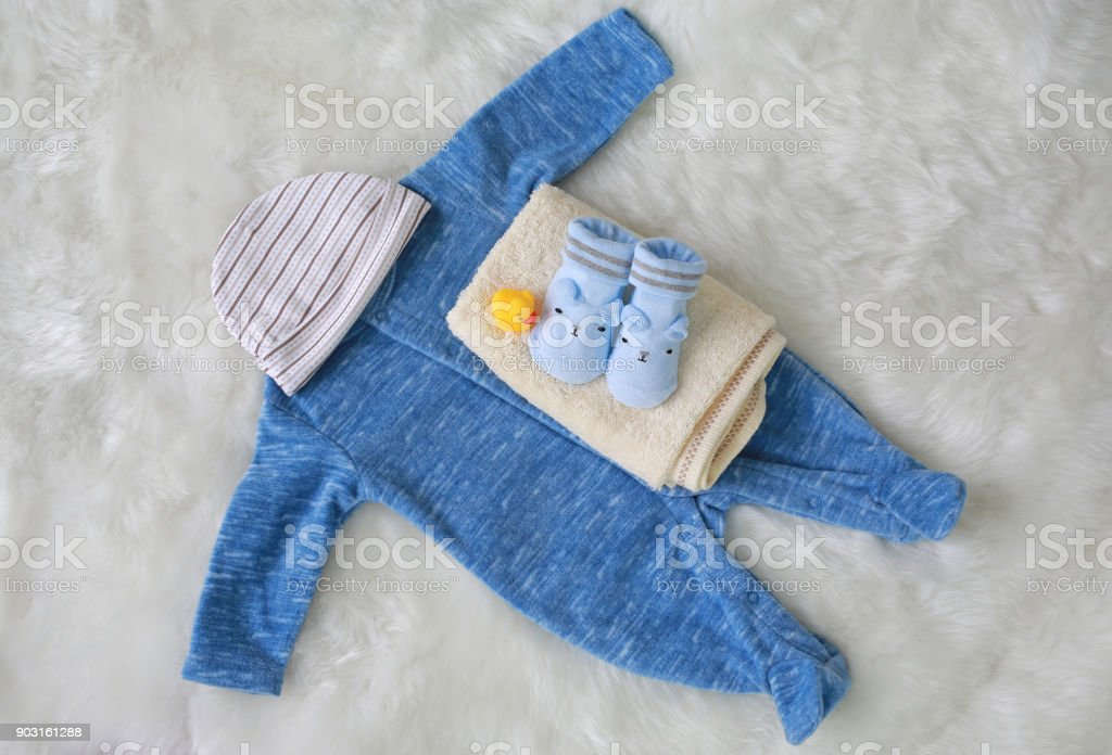 Collection items of bodysuits for newborn babies with socks and towel on white fur background. stock photo