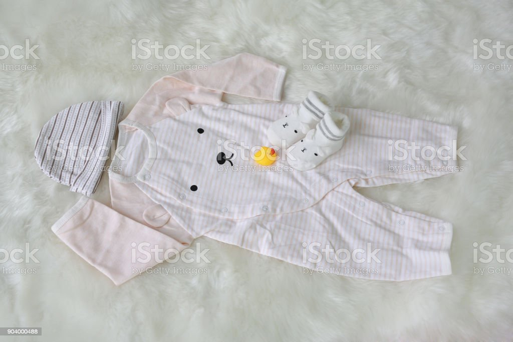Collection items of bodysuits for newborn babies with socks on white fur background. stock photo
