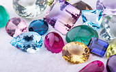 Collection mix colorful of gemstones jewelry on white sand.