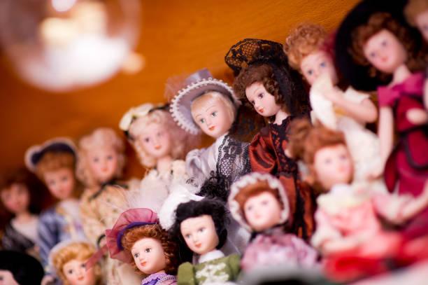 Una colección de muñecas antiguas en vestidos retro. Una muñeca está enfocada, el resto está desenfocada. Concepto - foto de stock